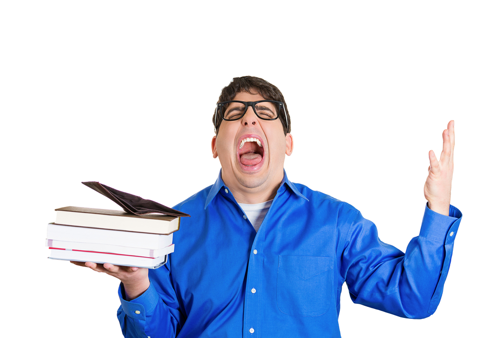 Closeup portrait young funny looking guy upset screaming man with glasses holding books, empty wallet on top, anxious completely broke no money left after tuition was paid isolated on white background