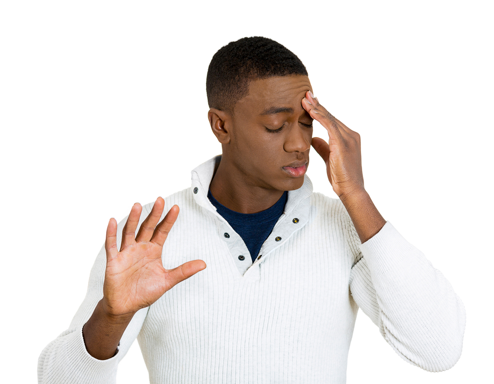 Closeup portrait, young, frustrated man with bad attitude giving talk to hand with palm outward, hand on head, isolated white background. Negative emotions, facial expression feelings, body language